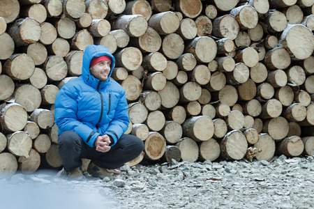 manhood: Squatting lumberjack at stack of logged firewood background outdoors in winter mountain fir forest