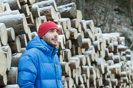 firewood background: Resting woodcutter at wall of cut firewood background outdoors in winter mountain conifer forest