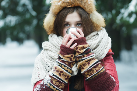 drink tea: Winter portrait of girl with hiding her face behind tourist vacuum flask cup with hot drink outdoors Stock Photo