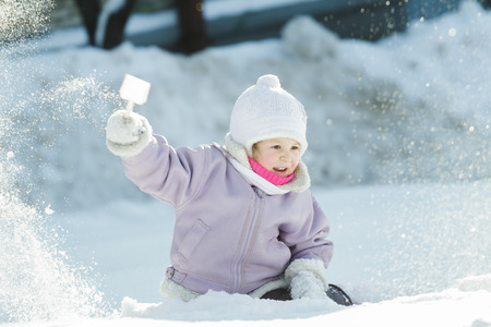 natural ice pastime: Toddler girl is tossing up natural snow with plastic toy shovel in frosty winter sunny day outdoors