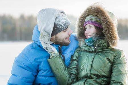 Junge Frau, die ihren Mann sanft umarmt mit auf der Hand im Winter frostigen Außen