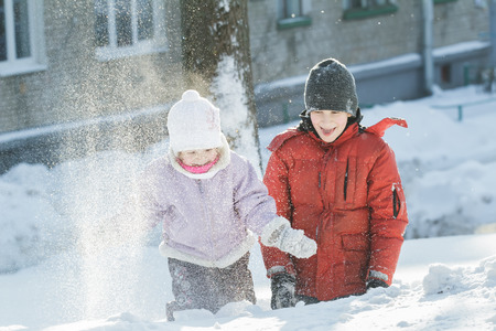 natural ice pastime: Two sibling children are playing outdoors by throwing snow grains in frosty winter sunny day