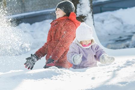 Geschwister Kinder machen Schneesturm durch Schnee im frostigen Winter sonnigen Tag wirft oben draußen