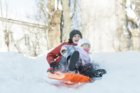 I fratelli stanno avendo in discesa divertimento sulla neve d'inverno cursore di plastica all'aperto Archivio Fotografico - 51897346