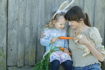 Woman with her toddler daughter are feeding domestic little Easter rabbit