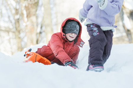 sibling: Teenage boy is chasing after his sibling sister outdoors on snow hill Stock Photo