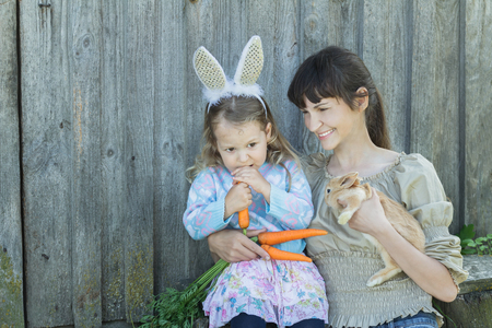 mother and baby deer: Woman and preschooler girl are with cute Easter rabbit and carrots in arms