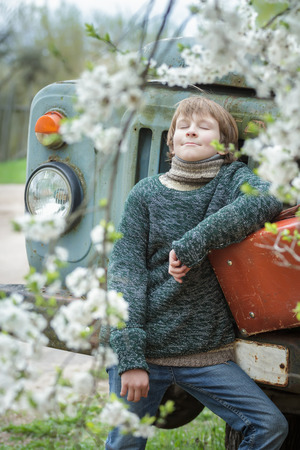 russet: Dreaming teenager with closed eyes is wearing knitted melange sweater outdoors with vintage russet suitcase during his travel Stock Photo