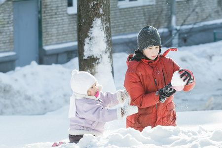 natural ice pastime: Two children are playing outdoors with plastic toy tool in snowy winter sunny day