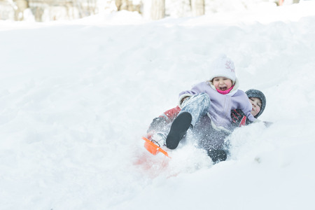 healthy girl: Two children are sliding down snowy hill outdoors on orange plastic modern toboggan for kids Stock Photo