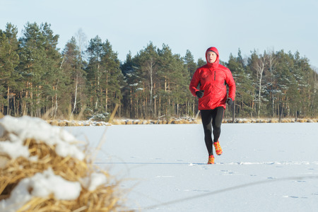 well built: Well built running man outdoors in winter snowy conifer forest