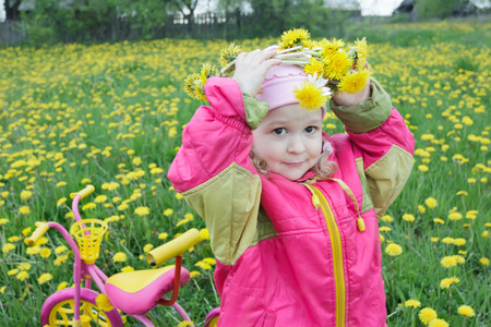 putting on: Two years old girl is putting on floral wreath made of live yellow dandelions flowers