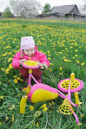 fuchsia color: Fuchsia color kids trike with yellow wheels and little toddler girl is exploring vehicle Stock Photo
