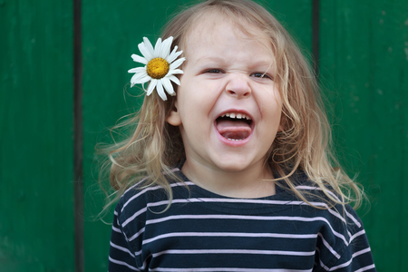 snarling: Head and shoulders portrait of two years old grimacing and snarling blonde girl with chamomile flower in her hair Stock Photo