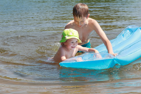 lilo: Sibling children are having fun with inflatable blue pool lilo in summer lake outdoor Stock Photo
