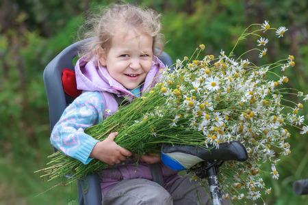 enfant banc: Portrait de l'�quitation sur le si�ge de l'enfant � v�lo petite fille blonde avec bouquet de chamomiles Cutted sauvages dans les mains