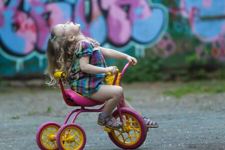 tunic: Preschooler girl wearing checked tunic is riding yellow and pink tricycle