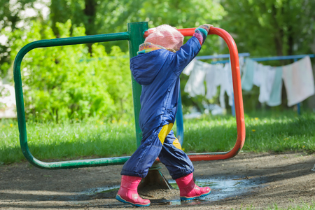 boilersuit: Little girl in blue boilersuit is rotating vintage manually roundabout carousel at drying linens and green grass background