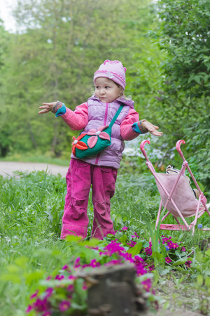 hooded vest: Little girl with pink toy stroller is making helpless shrug gesture near purple primula flowerbed Stock Photo