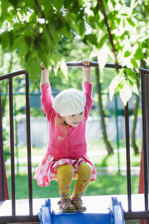 three years old: Three years old girl is playing at playground slide and hanging on crossbar Stock Photo