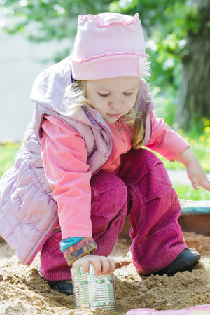 squatting down: Three years old girl is playing with metal tin can in playground sandbox