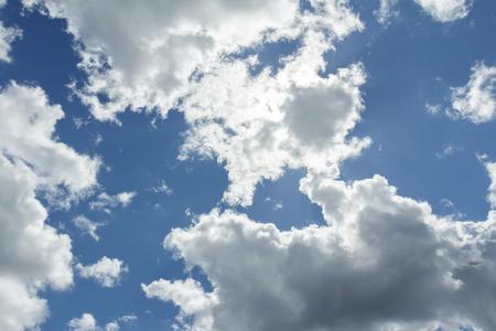 ultramarine blue: White clouds in ultramarine blue sunny sky with sun backlight