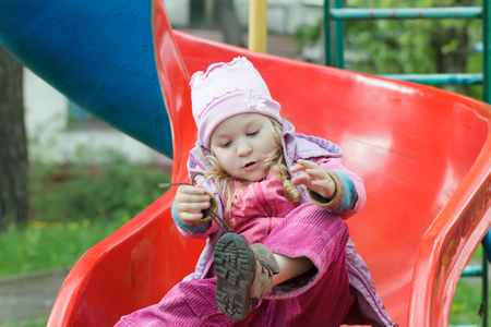 hooded vest: Little girl is sitting on red plastic playground slide and tying shoelaces of her kids trainers