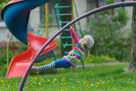 jungle gym: Active little girl is hanging on jungle gym outdoors on spring playground Stock Photo