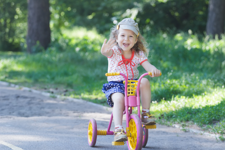 Two year-old laughing girl is wearing corduroy flat cap and polka-dotted costume cycling kids pink and yellow tricycle