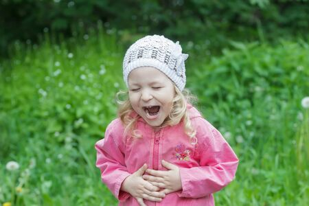 Little Caucasian girl is bending with belly laughter in spring green garden