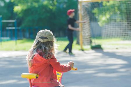 futbol infantil: Vista posterior de la ni�a est� mirando a jugar muchacho en ni�os de tierra de f�tbol callejero Foto de archivo