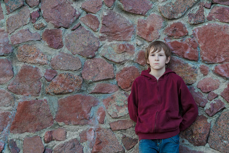 reverie: Teenage boy is wearing burgundy hooded sweatshirt with vertical zipper leaning red granite boulders wall Stock Photo