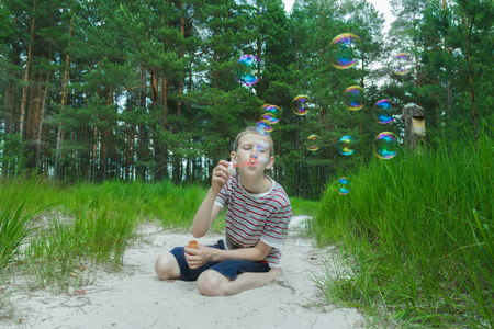 pinewood: Boy is making soap bubbles on white sand dunes beach at pinewood background Stock Photo