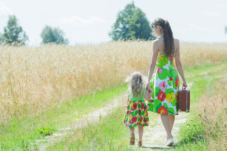 Back view full length portrait of walking mother and her little daughter on summer rural country road