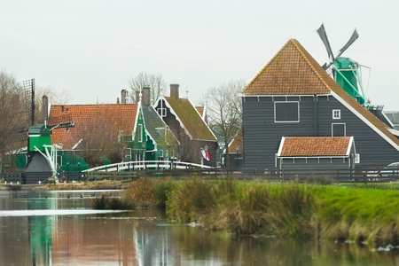 netherlandish: Traditional rural settlement in old Holland with old windmills and calm river Stock Photo