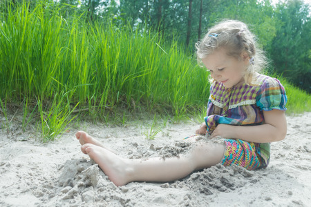 burying: Little girl is playing on beach dune and burying herself in white sand at summer pinewood background
