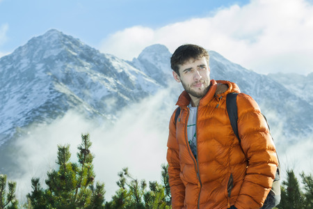 scrambling: Handsome mountaineer is posing at astonishing snowy rocky landscape background