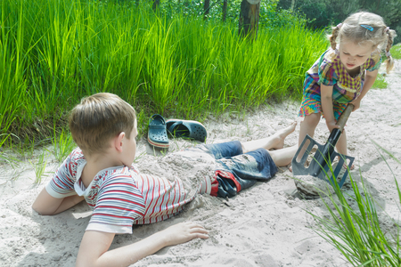 pinewood: Sibling children are playing on beach dune and burying each other in white sand at pinewood background