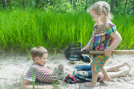 pinewood: Sibling girl and boy are digging on beach dune and burying each other in white sand at pinewood background