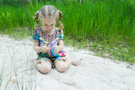 girl looking up: Little girl is playing on beach dune and examining little yellow leaf in her hand Stock Photo