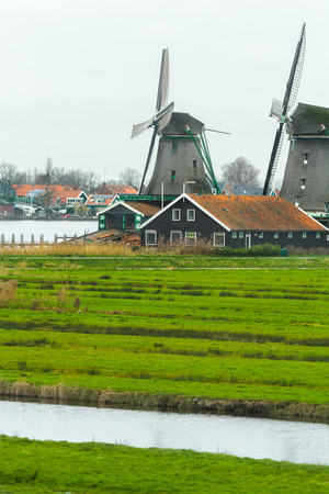 netherlandish: Traditional Dutch windmills and old farm house on calm river bank