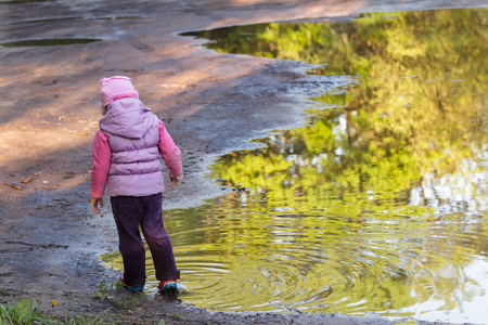 hooded vest: Back view of little girl exploring large spring puddle is wearing purple nylon and pink bucket hat Stock Photo