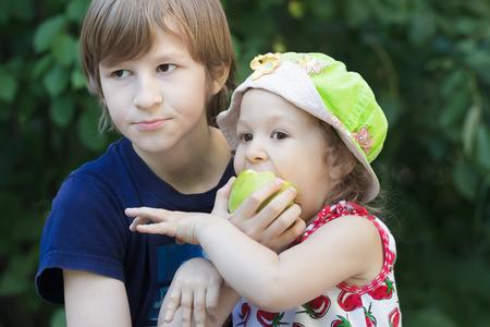 poco: hijos de hermanos comparten fruta verde manzana al aire libre Foto de archivo