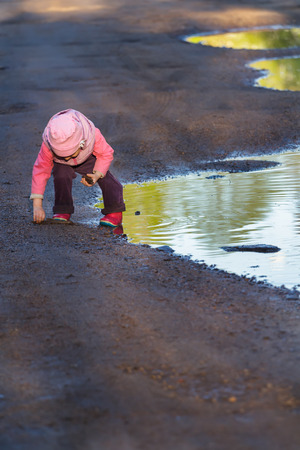 hooded vest: Little girl is bending to the ground playing in big spring puddle wearing purple nylon and pink bucket hat Stock Photo