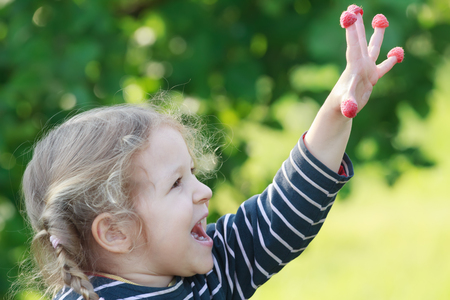 splayed: Happy two years old blonde girl is showing red garden raspberry fruits