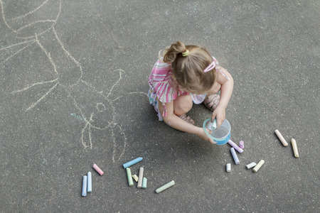 Sidewalk chalking of little blonde girl wearing pink ruffle skirt with floral pattern Archivio Fotografico