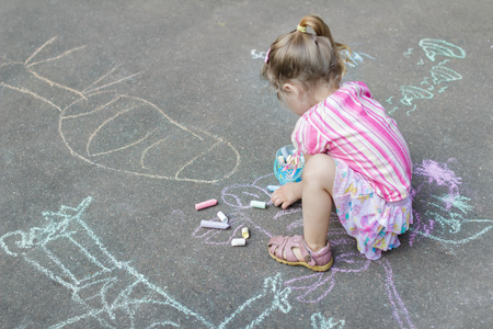 Sidewalk chalk drawings of little Caucasian girl wearing pink ruffle skirt with floral pattern Stock Photo