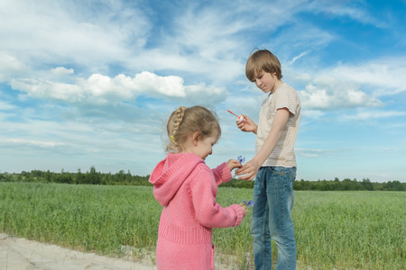 oat field: Sibling children are sharing blue cornflowers and soap bubbles in green summer oat field Stock Photo