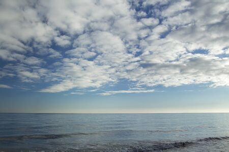 navy blue: Stratocumulus clouds over navy blue sea water waves Stock Photo