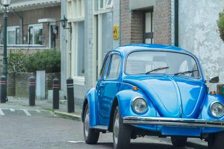 ultramarine blue: Vintage ultramarine blue classic car is on city parking outdoors Stock Photo